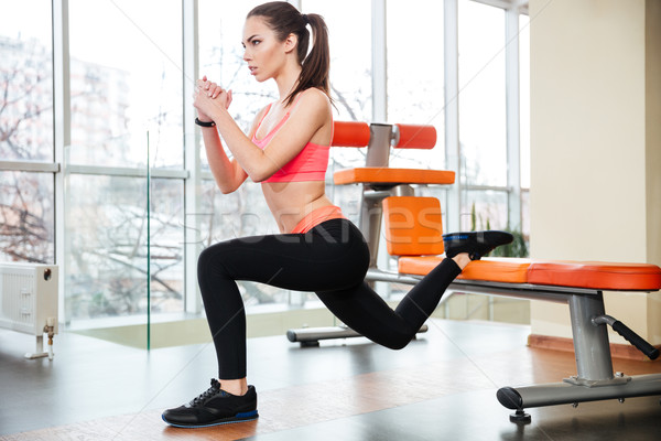 Sportswoman doing squats using bench in gym Stock photo © deandrobot