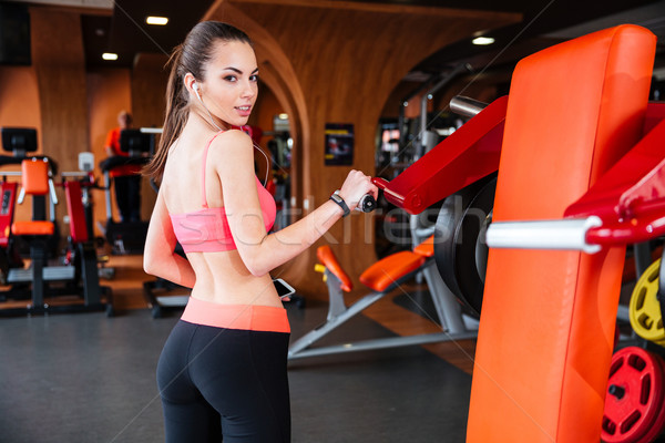 Sportswoman listening to music and training in gym Stock photo © deandrobot