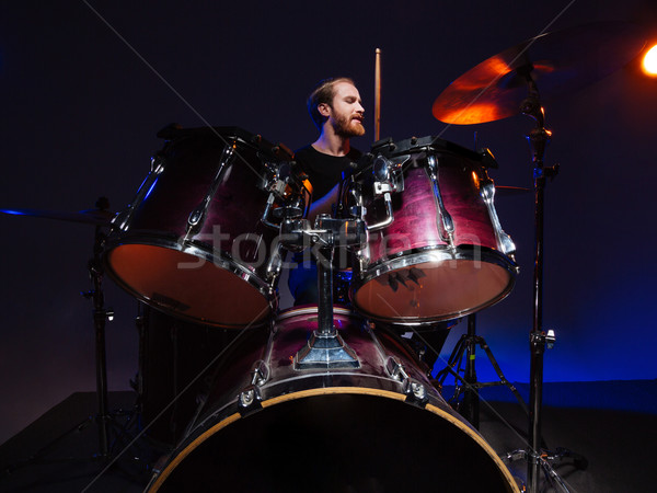 Attractive bearded man drummer sitting and playing on his kit Stock photo © deandrobot