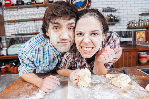 Couple with flour on faces kneading dough Stock photo © deandrobot