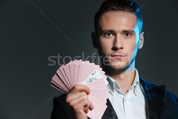 Stock photo: Serious young man magician holding playing cards with ace