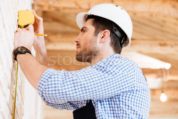 Builder doing measures in a new house Stock photo © deandrobot