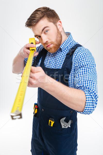Concentré barbu jeunes travailleur mètre à ruban travaux Photo stock © deandrobot