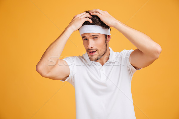 Gorgeous confident young sportsman touching his hair and posing Stock photo © deandrobot
