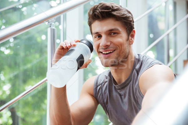 Happy sportsman drinking water in gym Stock photo © deandrobot