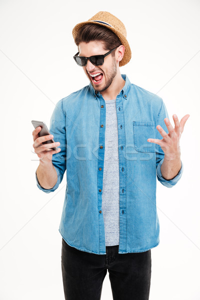 Close-up portrait of angry man shouting at his smartphone Stock photo © deandrobot