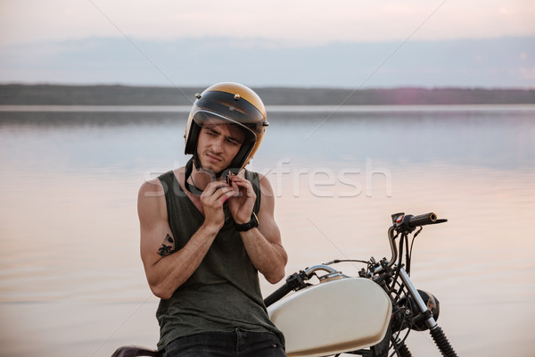 Man tries to put off his helmet sitting on motorcycle Stock photo © deandrobot