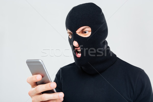 Mad aggressive man in balaclava standing and using mobile phone Stock photo © deandrobot