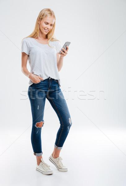 Tam uzunlukta portre genç kadın cep telefonu mutlu Stok fotoğraf © deandrobot