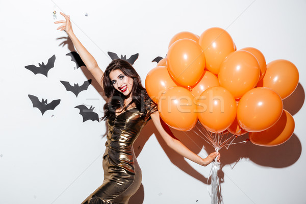 Cheerful woman with vampire makeup and orange balloons having fun Stock photo © deandrobot