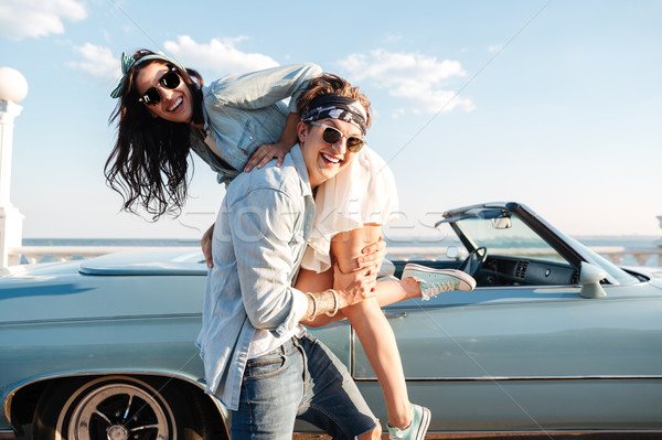 Man carrying his woman in front of vintage cabriolet Stock photo © deandrobot