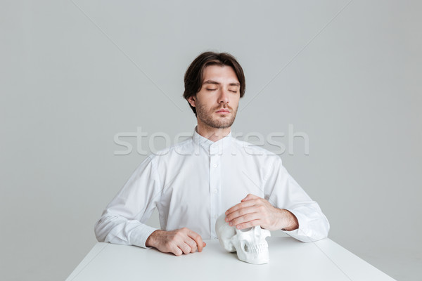 Man sitting with eyes closed holding fake skull at table Stock photo © deandrobot