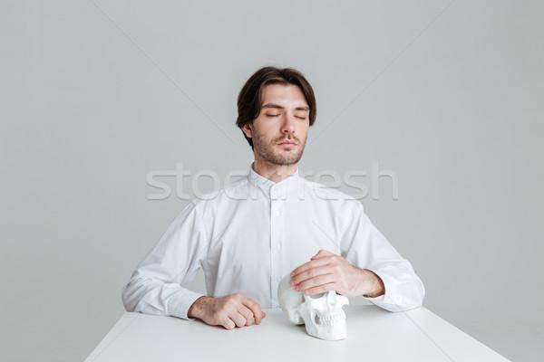 Homme séance faux crâne Photo stock © deandrobot
