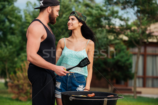 Couple standing and frying on barbeque grill outdoors Stock photo © deandrobot