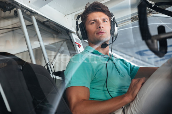 Serious young man pilot in cabin of private aircraft Stock photo © deandrobot