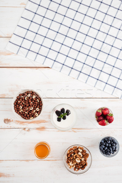 Berries, cereals, nuts, honey and plaid napkin Stock photo © deandrobot