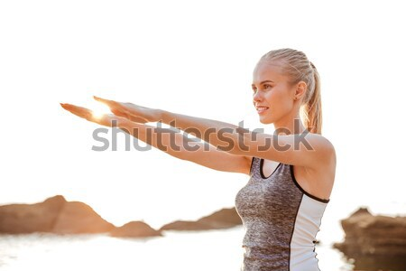 Stock photo: Beautiful woman stretching hands exercises during yoga on the beach