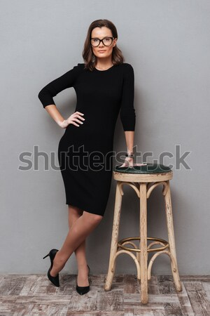 Beautiful smart woman sitting on the chair with arms folded Stock photo © deandrobot