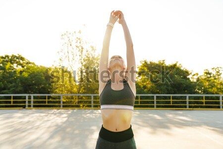 Portrait of a sports woman stretching leg outdoors Stock photo © deandrobot