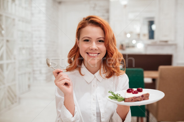 Redhead young happy woman eating cake in cafe. Stock photo © deandrobot