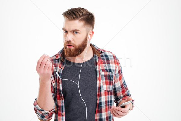 Unhappy irritated young man listening to music with smartphone Stock photo © deandrobot