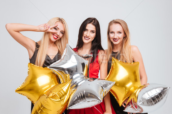 Three cheerful lovely girls holding star shaped balloons Stock photo © deandrobot