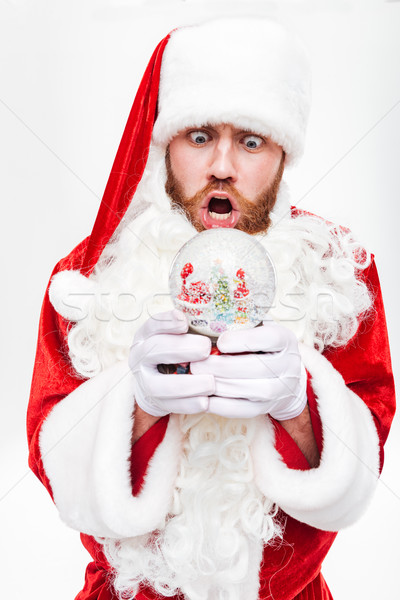 Shocked astonished man santa claus standing and holding snow ball Stock photo © deandrobot