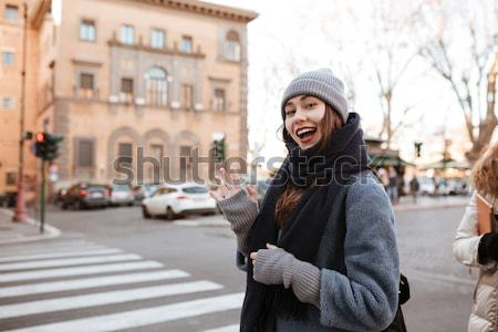 Smiling woman trying to catch a taxi on the street Stock photo © deandrobot