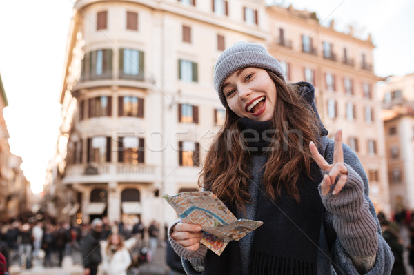 Stock photo: Cheerful woman using map and showing peace sign in city