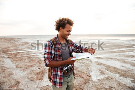 Pensive man with backpack sitting and drinking from hip flask Stock photo © deandrobot