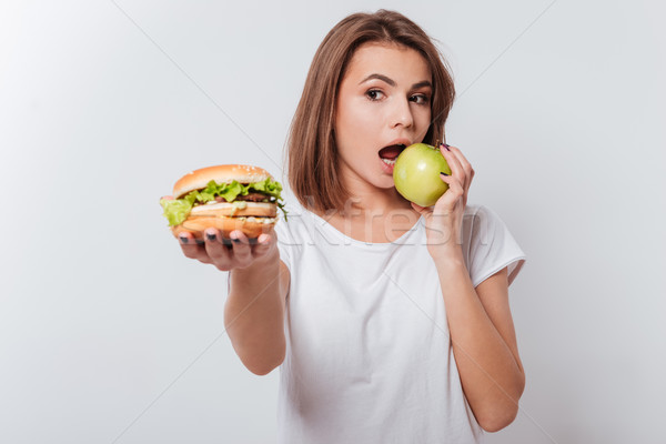 Serious young woman holding fastfood and eating apple Stock photo © deandrobot