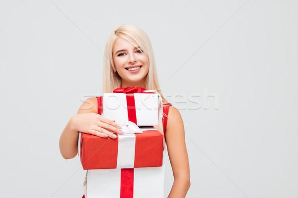 Derűs nő vörös ruha halom karácsony ajándékok Stock fotó © deandrobot