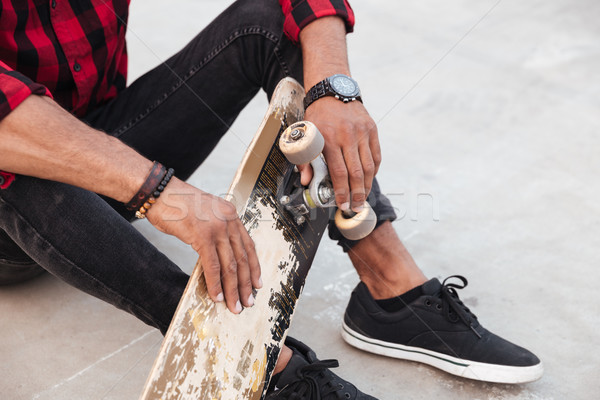Cropped dark skinned young man sitting near his skateboard Stock photo © deandrobot