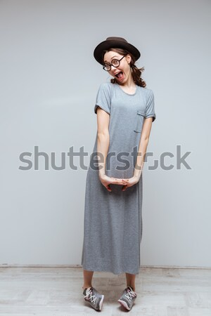 Vertical image of Shy Female nerd posing in studio Stock photo © deandrobot