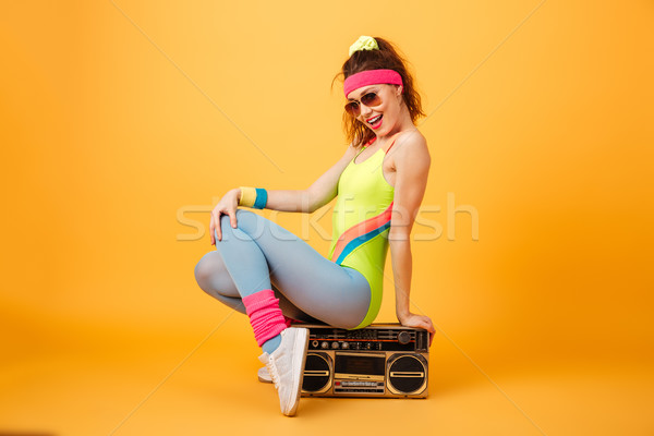 Smiling cute young sportswoman in sunglasses sitting on retro boombox Stock photo © deandrobot