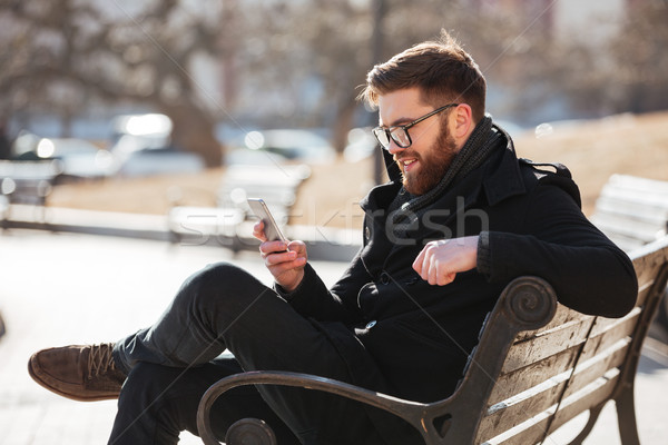 Cheerful man sitting and using smartphone in the city Stock photo © deandrobot