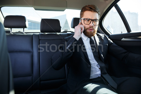 Frustrated business man in eyeglasses talking on mobile phone Stock photo © deandrobot
