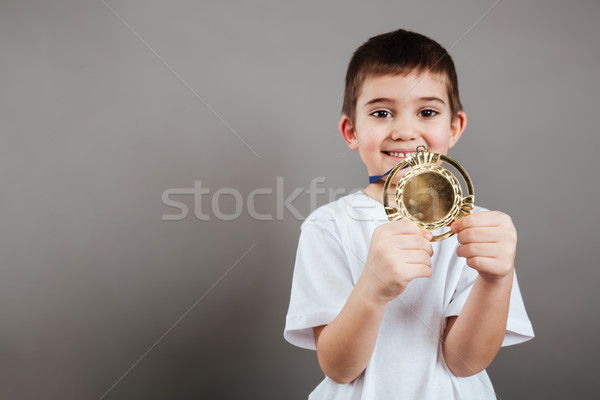 Cheerful little boy showing gold trophy medal Stock photo © deandrobot