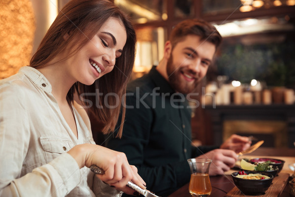 Amazing young loving couple sitting in cafe and eating. Stock photo © deandrobot