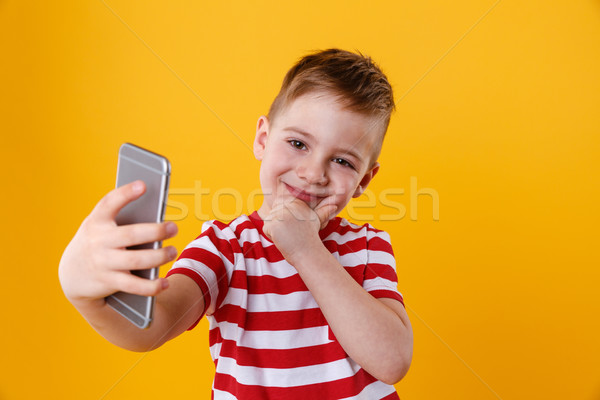Smiling little boy making selfie and thinking about something Stock photo © deandrobot