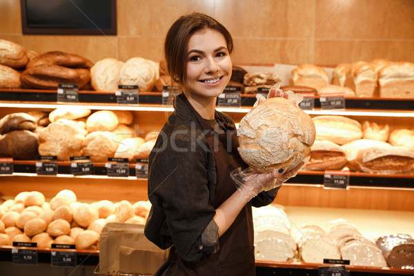 Cheerful woman in supermarket choosing pastries. Stock photo © deandrobot