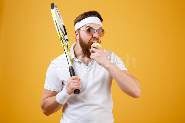 Hungry young tennis player bite tennis ball. Stock photo © deandrobot