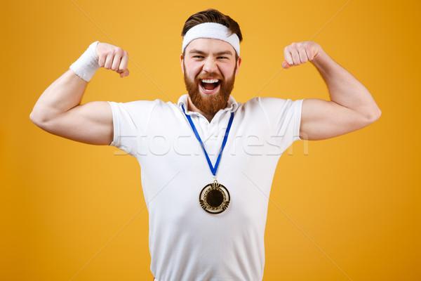 érzelmes fiatal sportoló érem mutat bicepsz Stock fotó © deandrobot