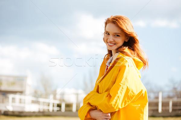 Portrait of a pretty happy girl in coat enjoying Stock photo © deandrobot