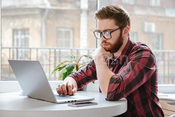 Serious bearded young man using laptop computer. Stock photo © deandrobot
