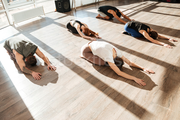 Group of relaxed young people doing yoga asana in studio Stock photo © deandrobot
