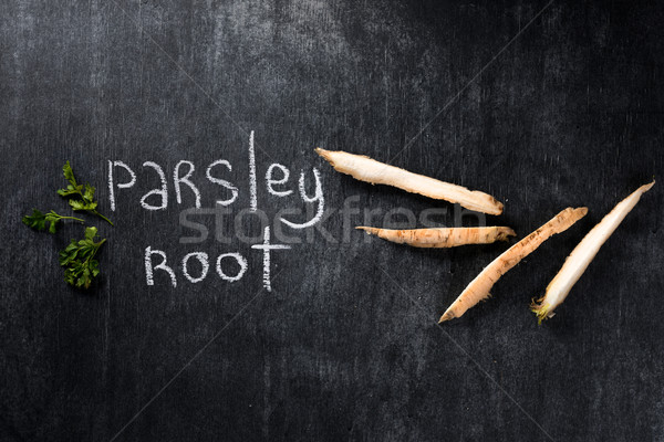Image of parsley root over dark chalkboard background. Stock photo © deandrobot