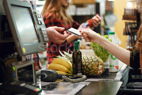 Stock photo: Cropped picture of young man gives credit card to cashier