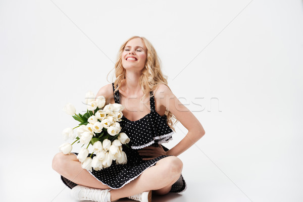 Nevet szőke nő ül padló virágcsokor virágok Stock fotó © deandrobot