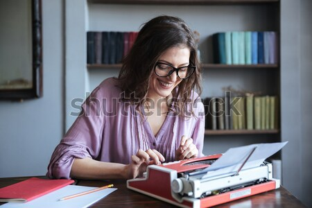 Brunette mature woman journalist in eyeglasses typing on typewriter indoors Stock photo © deandrobot